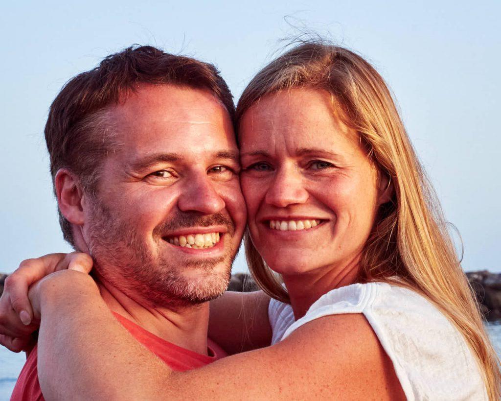 Glücklich lächelndes Pärchen genießt zusammen mit den Kindern den Urlaub
