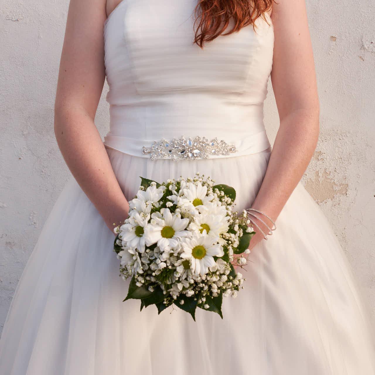 Braut steht mit Brautstrauß in Punta Brava auf Teneriffa beim Afterwedding Shooting