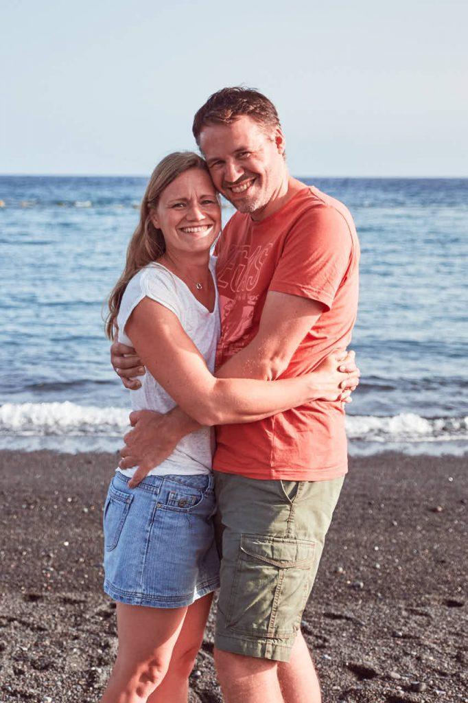 Umarmung eines Elternpaars beim Fotoshooting im Urlaub