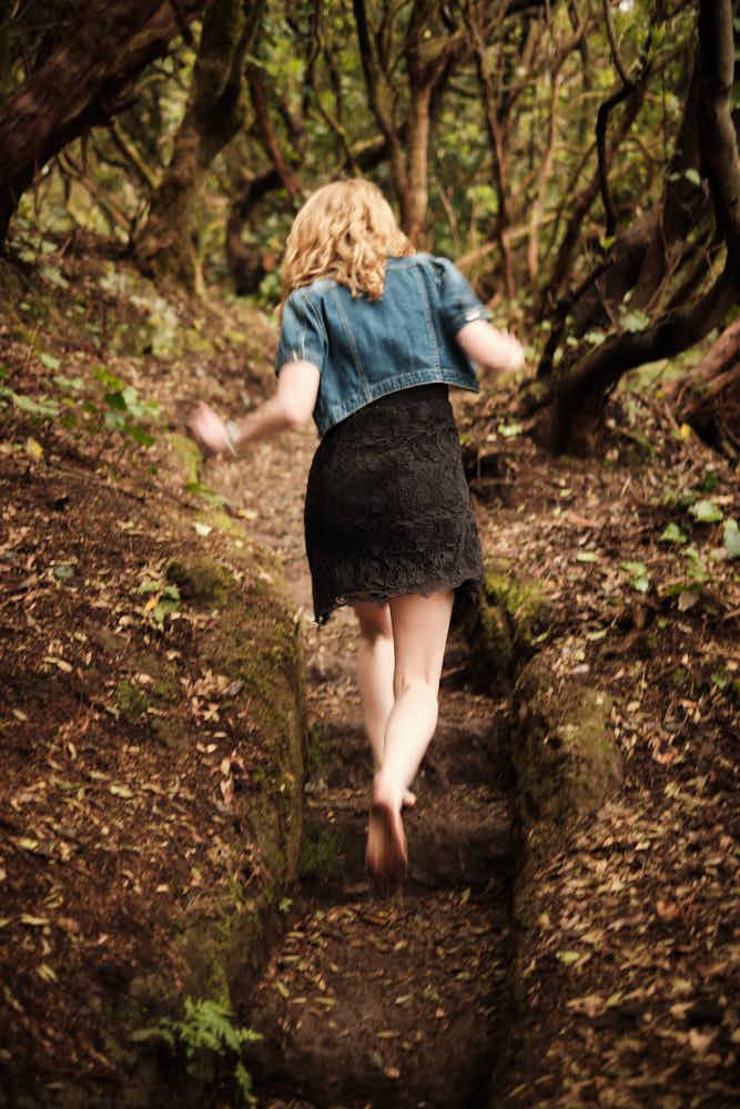 Mädchen läuft barfuss im Wald im Anagagebirge auf Teneriffa über eine Trepp im Märchenwald