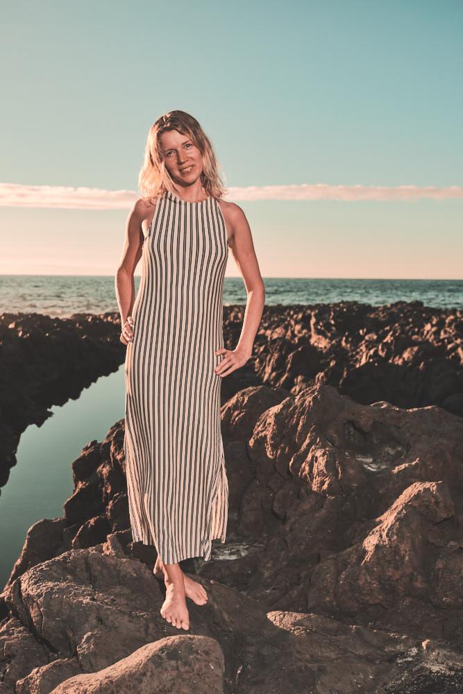 Business Frau steht an der Costa El Sauzal auf den Felsen im Sonnenuntergang
