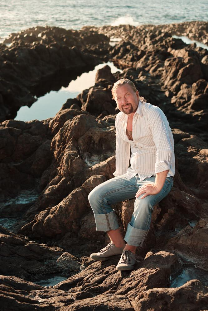 Trainer sitzt beim Shooting mit Deutscher Fotograf Kanaren Ela & Chris auf Felsen