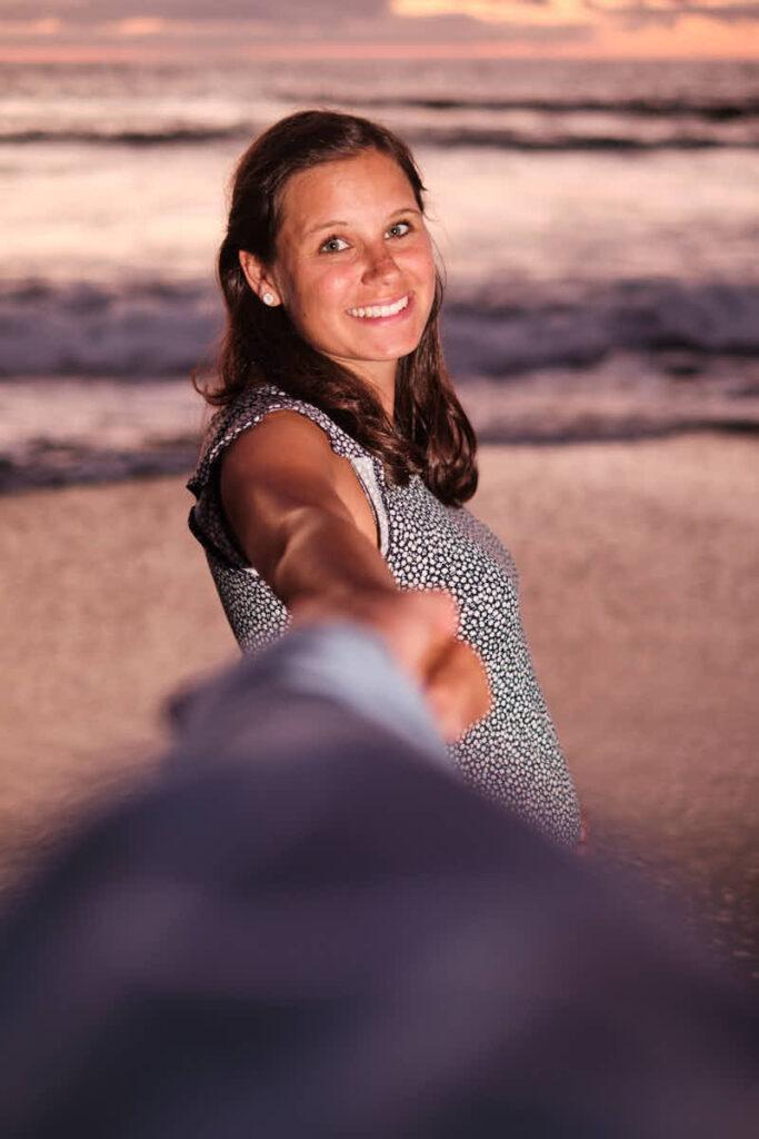 Im Sonnenuntergang fotografieren Fotograf Ela und Chris den Babybauch beim Fotoshooting am Strand