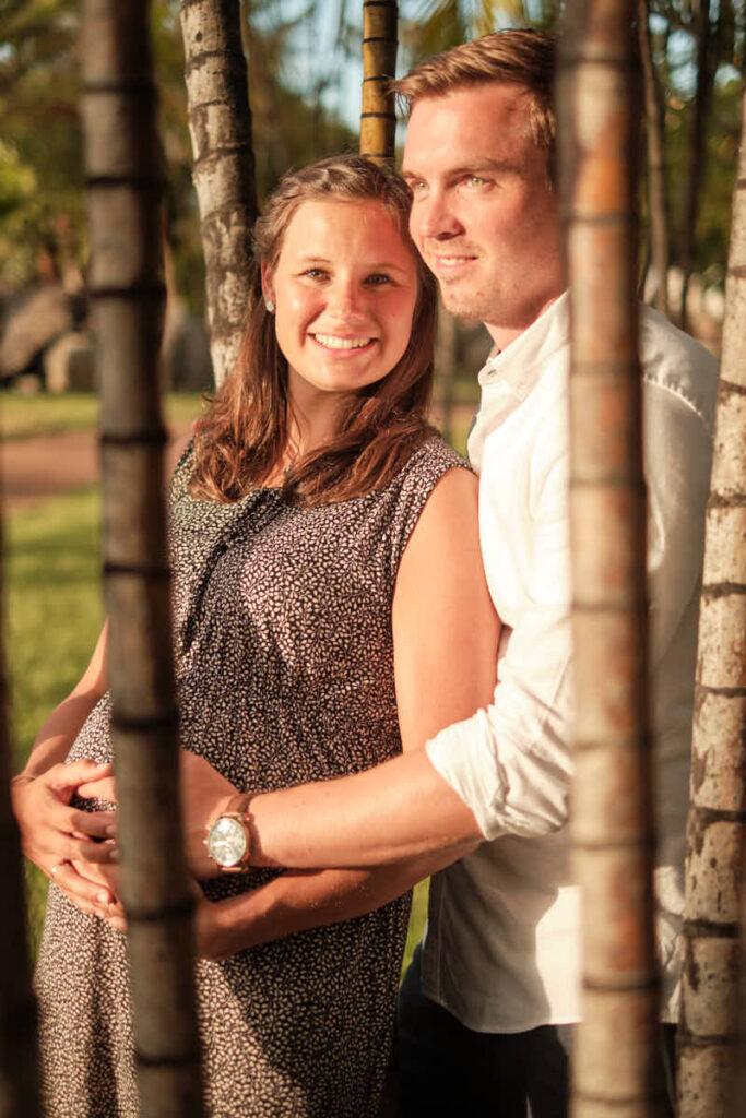 Die Eltern genießen die warme Sonne beim Babybauch Fotoshooting mit Fotograf Ela und Chris im Park im Urlaub
