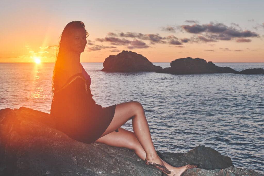 Deutscher Fotograf Ela und Chris fotografieren hübsches Mädchen barfuss am Strand von Teneriffa auf den Felsen im Fotoshooting im Urlaub