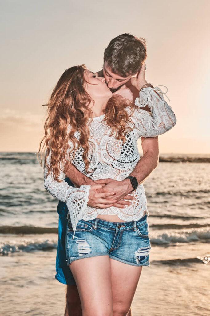 Die Eltern küssen sich im Sonnenuntergang am Strand im Urlaub während Deutscher Fotograf Ela und Chris ein schönes Urlaubsbild macht und die Emotion fest hält
