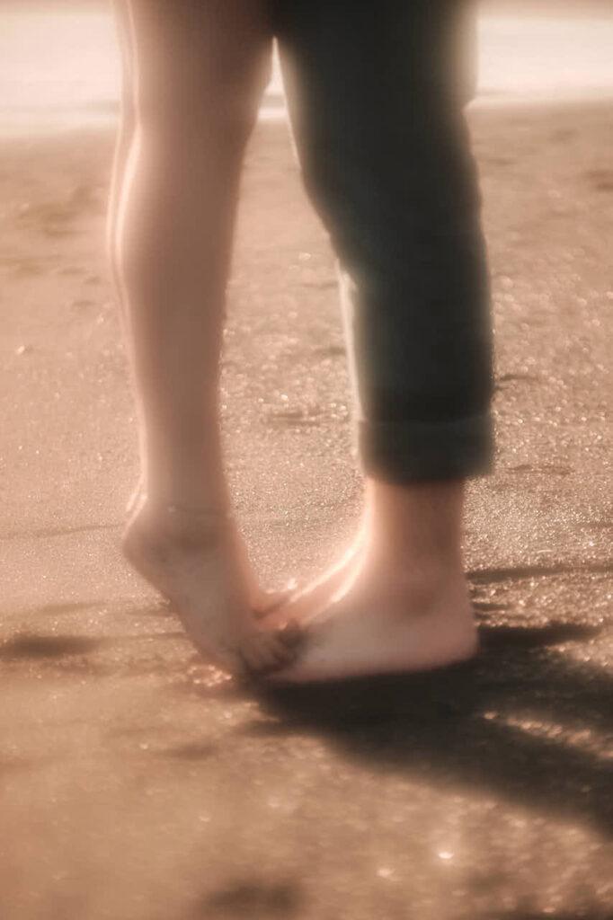Mädchen steht barfuss am Strand und küsst beim Fotoshooting mit Ela & Chris Deutscher Fotograf Kanaren