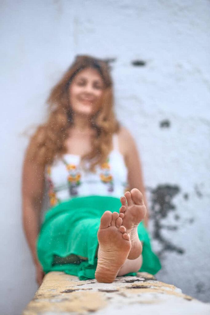 Mädchen zeigt beim Familien Fotoshooting mit Deutscher Fotograf Ela und Chris seine nackten Füße barfuß in der Sonne im Urlaub