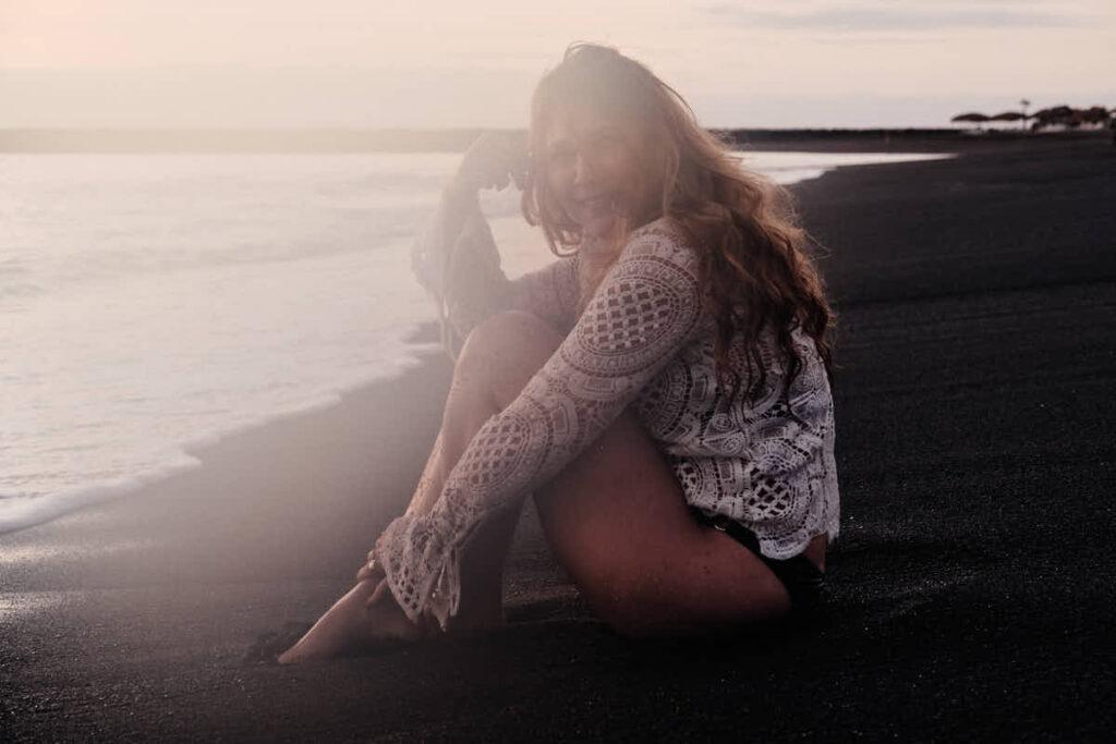 Mädchen sitzt im Bikini im Urlaub barfuß am Strand beim Familienshooting mit Deutscher Fotograf Ela und Chris und es entsteht ein Bild im David Hamilton Blur Stil